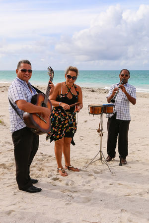 Trio ensemble performing on the beach, Cuba, Varadero Cuba. Varadero Beach Real People Men Sky Playing Music Guitar Performance Drums Trio Standing Outdoors Sand Musicians Cuba A Vacations Varadero Lifestyles Ensemble Young Adult Musical Instrument Casual Clothing Leisure Activity Horizon Over Water