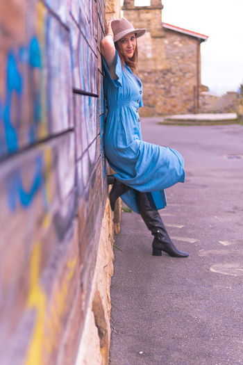 Side view portrait of woman standing by wall outdoors