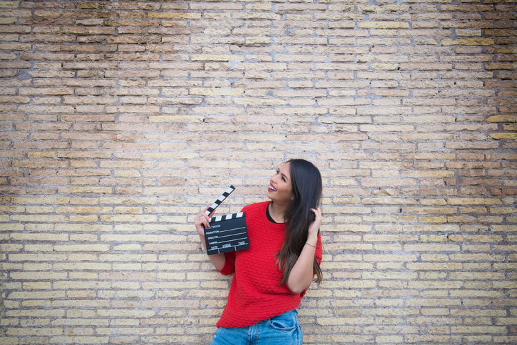 Young Woman Holding Film Slate While Standing By Brick Wall
