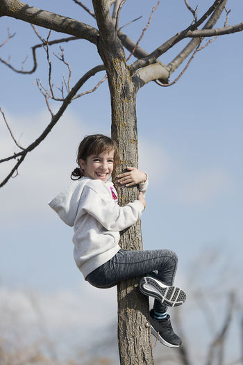 Ten-year-old girl climbing on a tree looking at the camera. Horizontal shot with natural light Bare Tree Boys Branch Casual Clothing Childhood Day Elementary Age Full Length Happiness Leisure Activity Lifestyles Looking At Camera Nature One Person Outdoors People person Portrait Real People Rope Swing Sky Smiling Standing Tree Tree Trunk