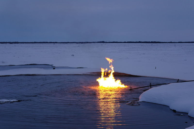 Burning water in Siberia Beauty In Nature Burning Fire Fire - Natural Phenomenon Flame Heat - Temperature Nature Reflection Sky Water