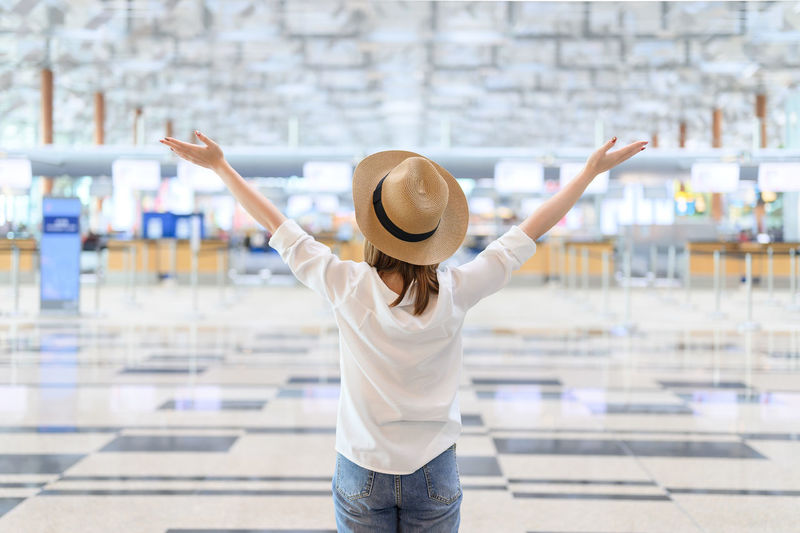 Rear view of woman wearing hat with arms raised standing at airport