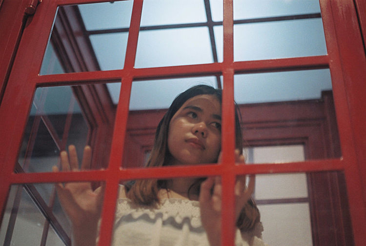 Close-up of woman looking telephone booth
