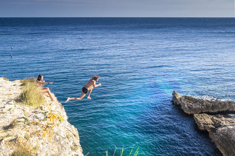 Man jumping by woman on rocks over sea against sky