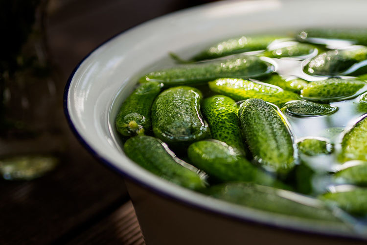 Close-Up Of Cucumbers In Water Filled Container On Table