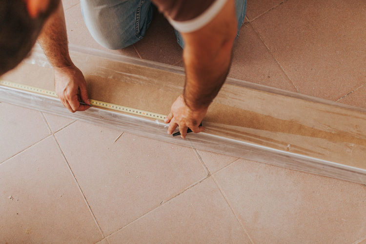 Midsection of man working on hardwood floor at home