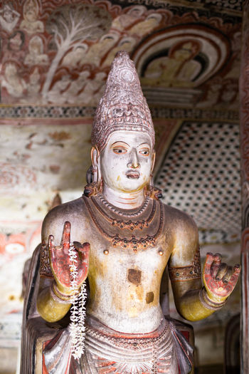 A Buddhist statue in a cave in Sri Lanka. Human Representation Religion Belief Sculpture Spirituality Male Likeness Art And Craft Representation Statue Creativity Place Of Worship No People Building Architecture Built Structure Indoors  Idol Ornate Buddhism Temple