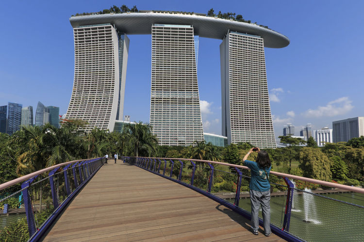 Singapore, Singapore - October 16, 2018: Young woman taking a picture of the Marina Bay Sands hotel from the gardens by the bay Singapore ASIA Gardens By The Bay Orchard Marina Bay Sands Flower Dome Cloud Forest Dome Arab Street Haji Lane, Singapore Modern Art Museum Ocean