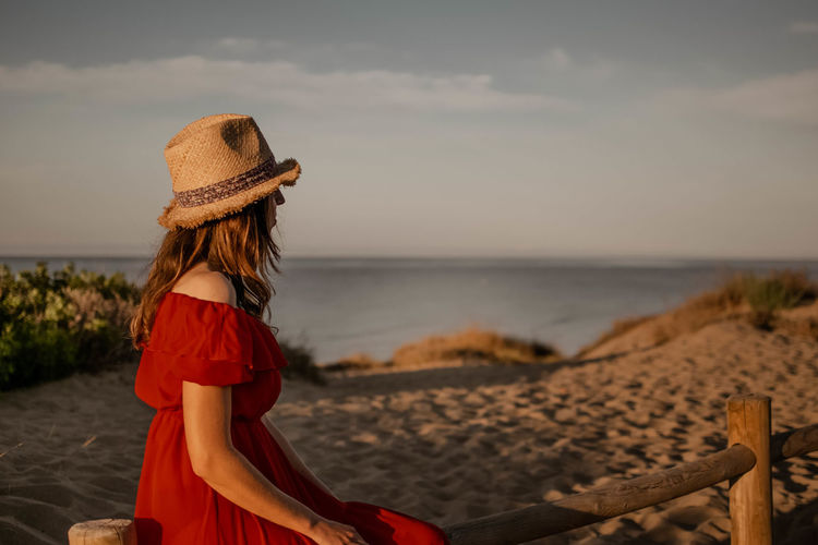 Side view of woman wearing hat sitting against sea and sky