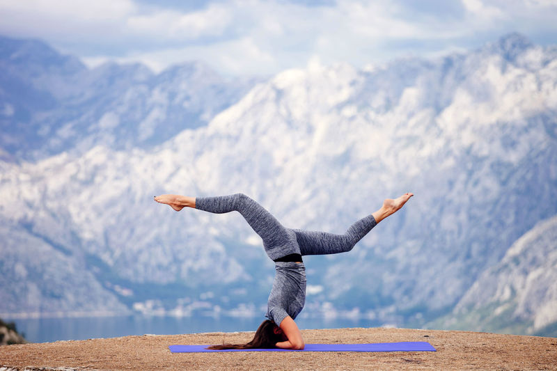 Woman Practicing Yoga Against Snowcapped Mountains