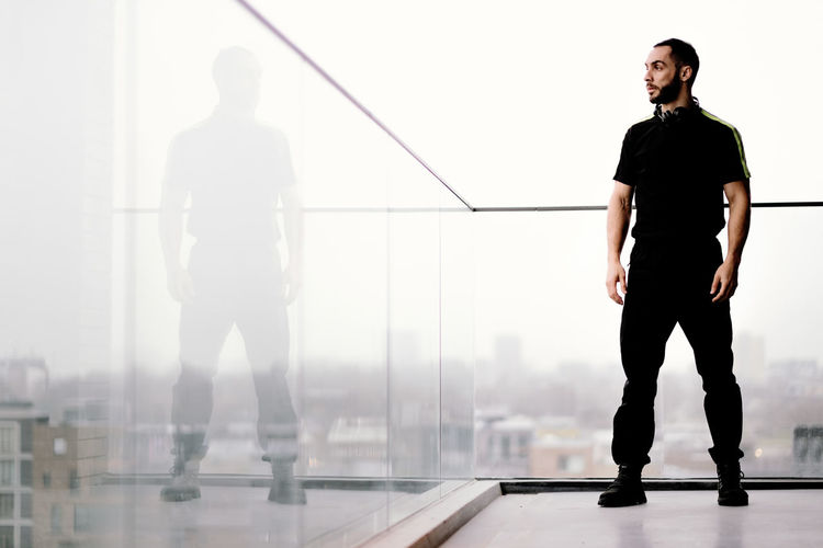 Full length of silhouette man standing against wall