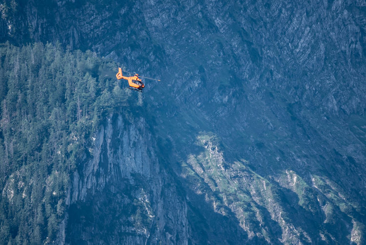 Low angle view of helicopter flying against mountain