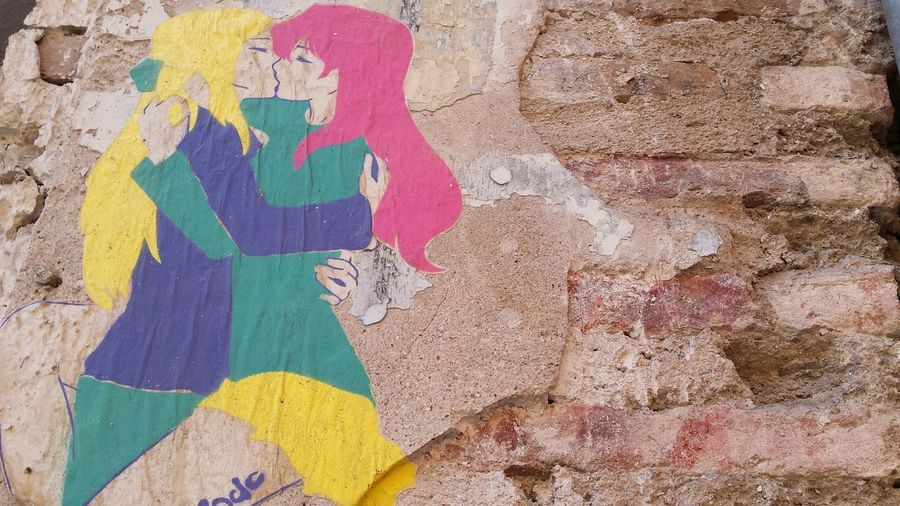Mural of lesbian couple kissing on weathered wall
