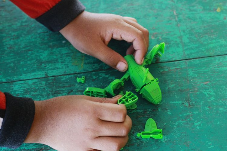 Cropped hands of child playing with green toy at table