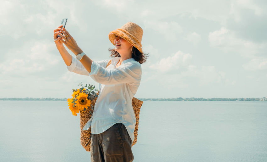 Portrait of beautiful woman wearing straw hat at seaside. girl taking selfie during vacation.