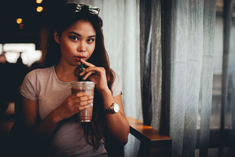 Portrait of young woman drinking iced coffee in cafe