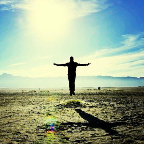 Silhouette man levitating above grassy field