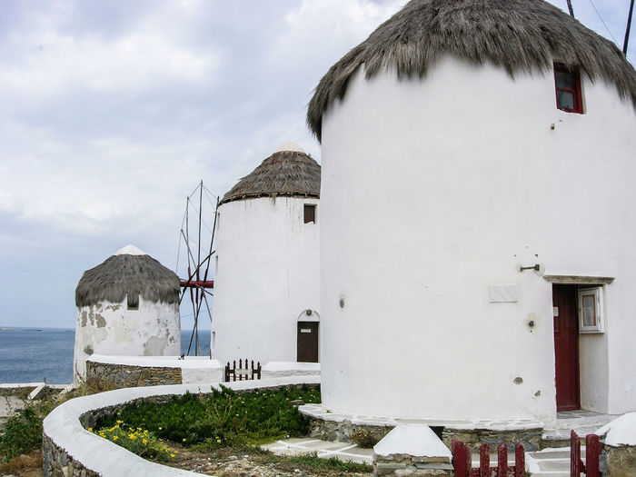 Traditional windmills at mykonos against cloudy sky