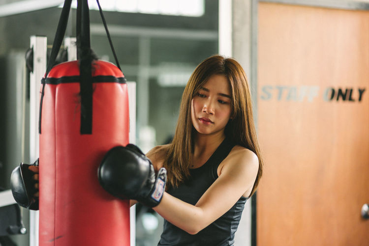 Confident Young Woman Holding Punching Bag While Standing In Gym