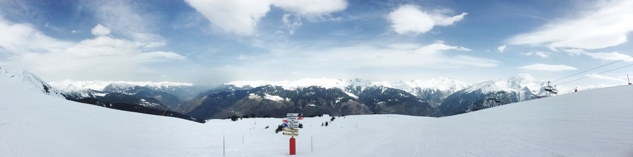 Panoramic view of people skiing on snowcapped mountain against sky