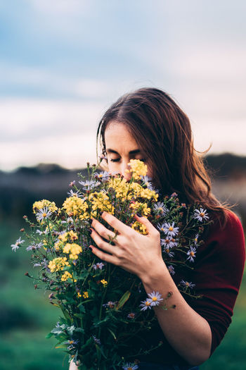 Woman with long brown hair in red sweater thoughtfully holding bouquet of wild flowers in the nature