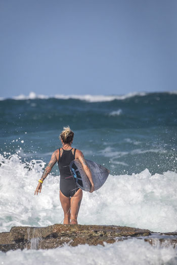 Rear view of woman with surfboard standing on rock at sea