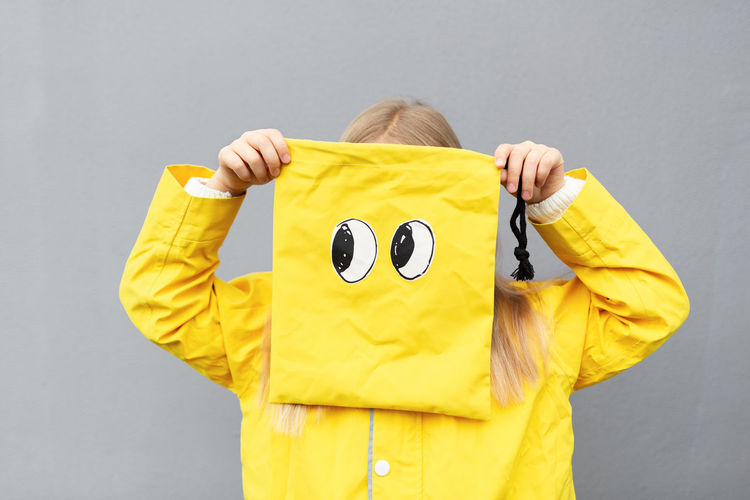 Girl holding yellow bag standing against gray background