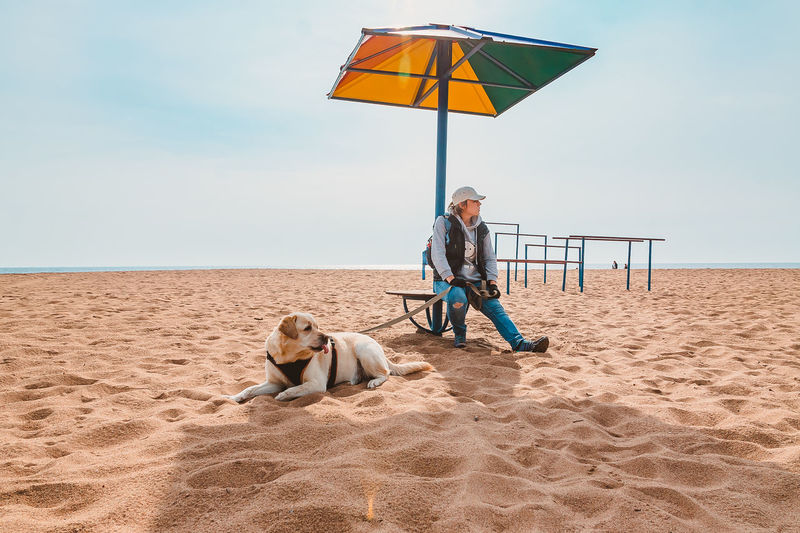 A tourist girl is resting with a dog under a chaise longue on an empty lonely beach