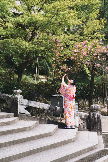 Kyoto, Japan - April 3, 2018: Young woman wearing traditional Japanese Kimono in public park Plant Tree Nature Day Real People Growth Architecture Full Length Rear View Staircase Outdoors People Standing Women Human Representation Representation Adult Religion Sculpture Arms Raised Human Arm Hanami Hanami Sakura  Park