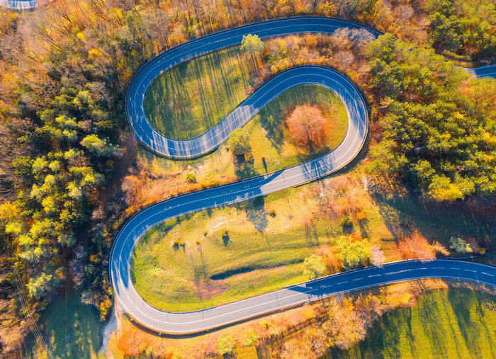 Aerial view of serpentine mountain road amidst trees during autumn