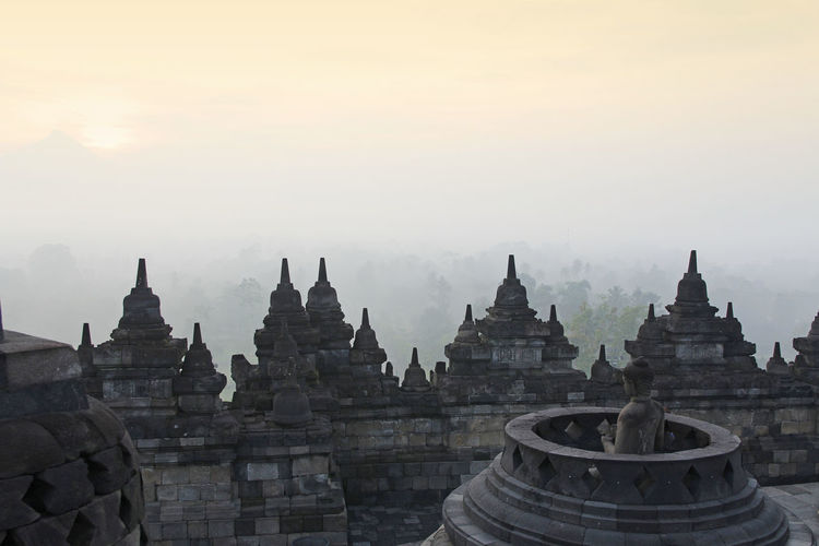 Borobudur Temple with the mysteries forest surrounding during sunrise, Yogyakarta, Indonesia Borobudur Temple Buddhist Yogyakarta Ancient Ancient Civilization Architecture Belief Building Exterior Built Structure Carving Fog Foggy Forest History No People Outdoors Place Of Worship Religion Sky Spirituality Sunrise The Past Travel Travel Destinations
