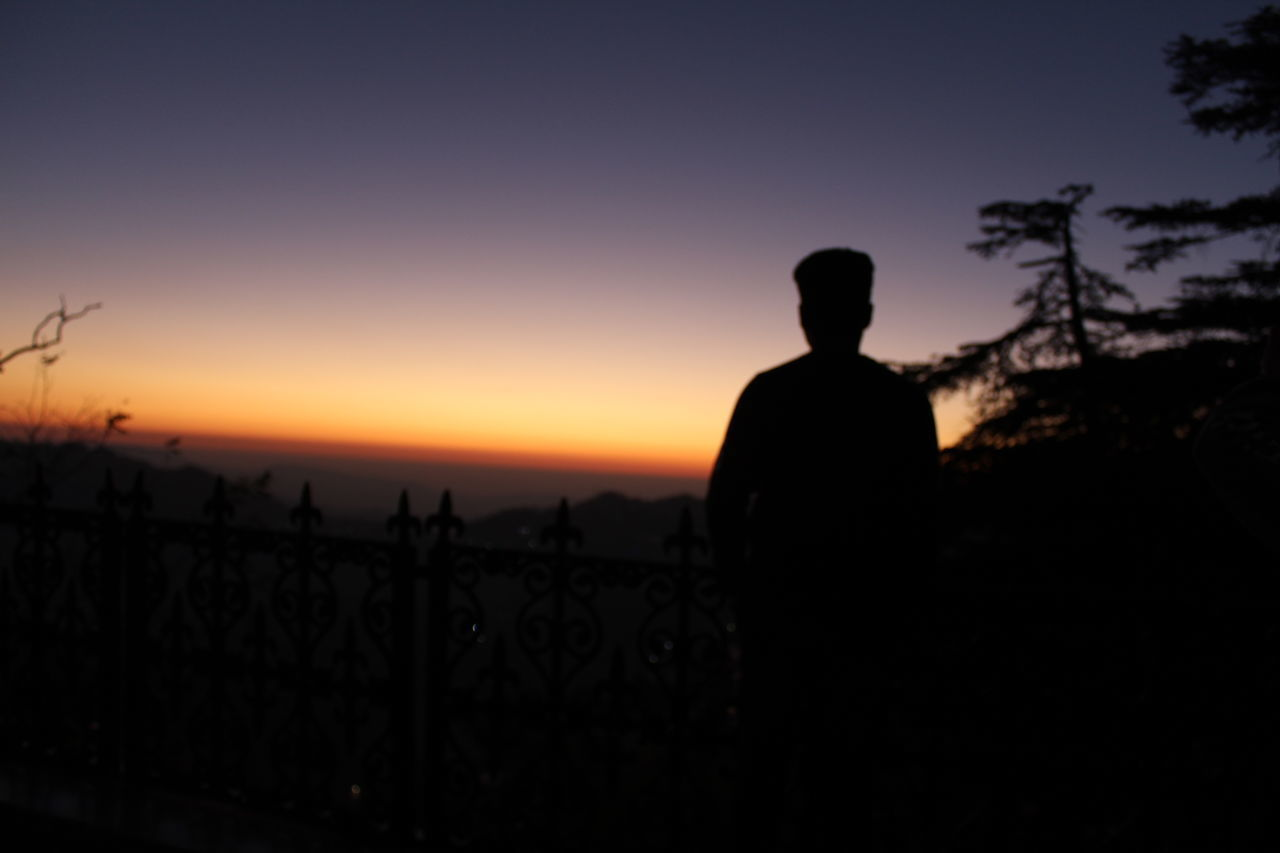 REAR VIEW OF SILHOUETTE MAN STANDING ON LAND DURING SUNSET