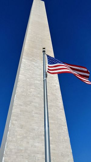 Low angle view of american flag by obelisk against clear blue sky