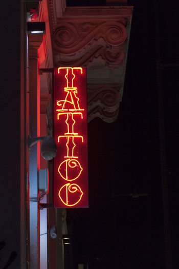 Low angle view of illuminated sign at night