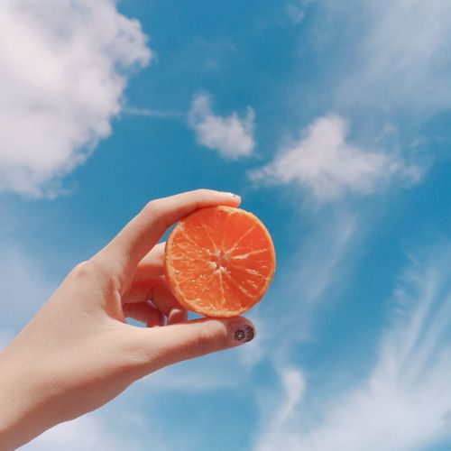 Cropped hand of woman holding orange slice against sky