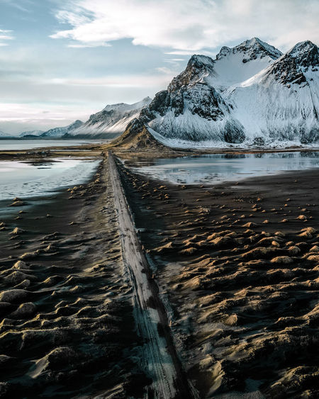 Scenic view of black sand beach and snowcapped mountain against sky