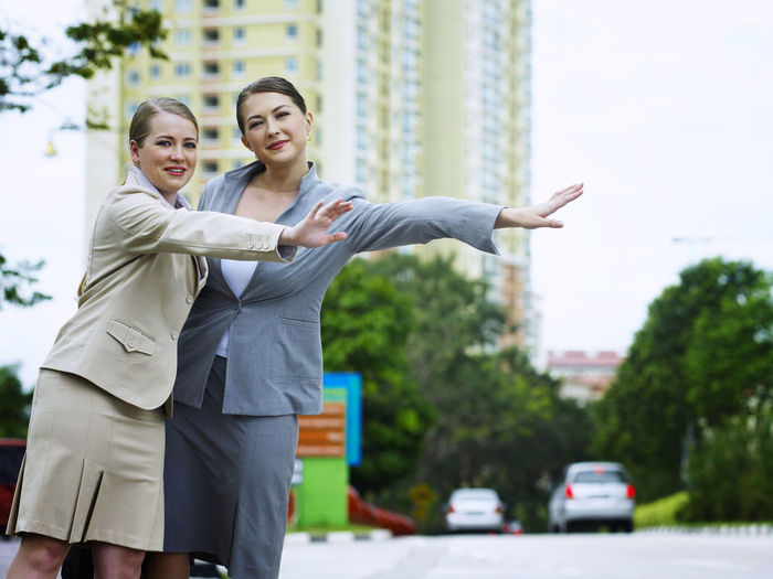 Businesswoman with colleague hitchhiking on road