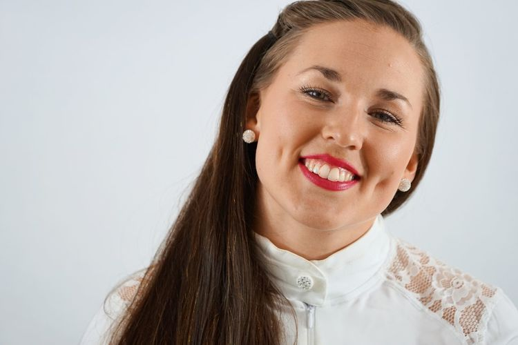 Close-up portrait of happy woman with dimples against white background