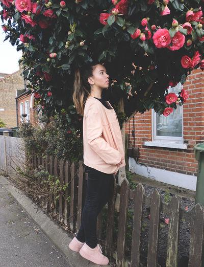 Side view of thoughtful woman looking away while standing below flowering tree