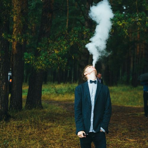 Young man exhaling smoke while standing in forest