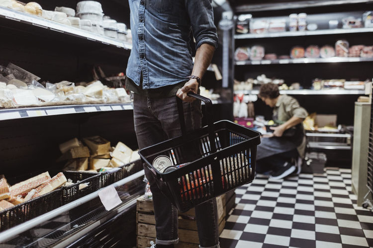 Full length of man standing in basket at store