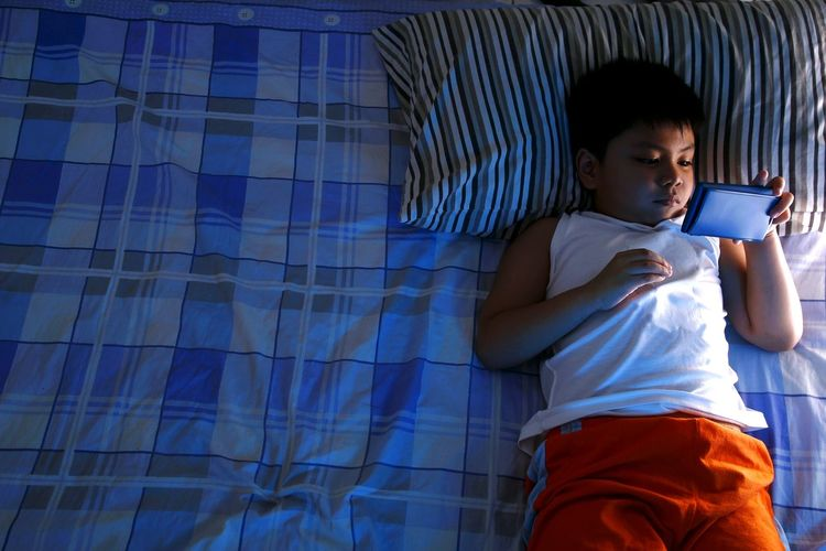 High Angle View Of Boy Using Smart Phone While Lying Down On Bed At Home