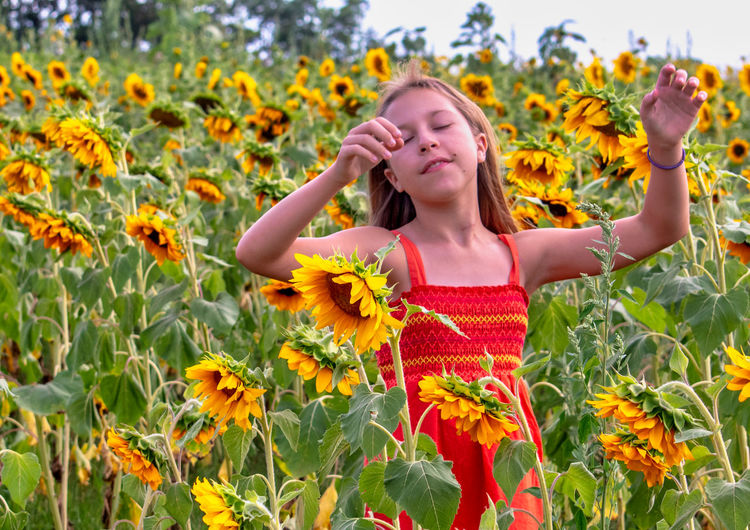 Low angle view of woman standing on sunflower field