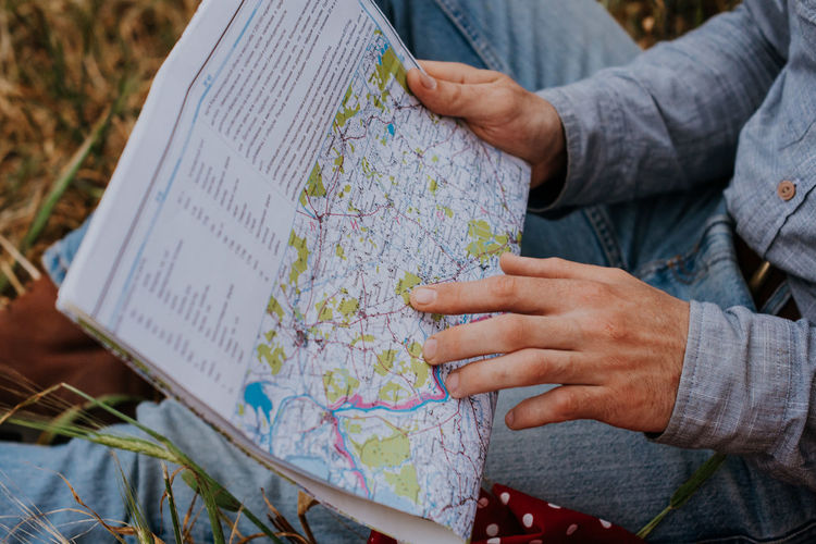Male hand on the road map