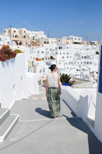 Rear view of woman on steps against buildings at santorini