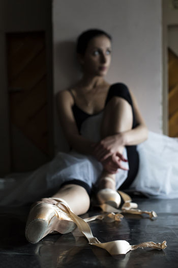 Thoughtful ballet dancer looking away while sitting on floor
