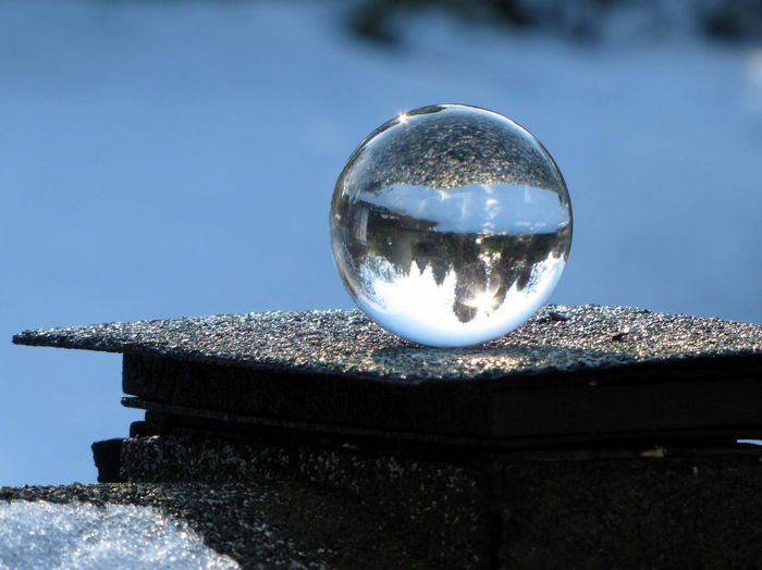 Reflection of crystal ball on glass against clear sky
