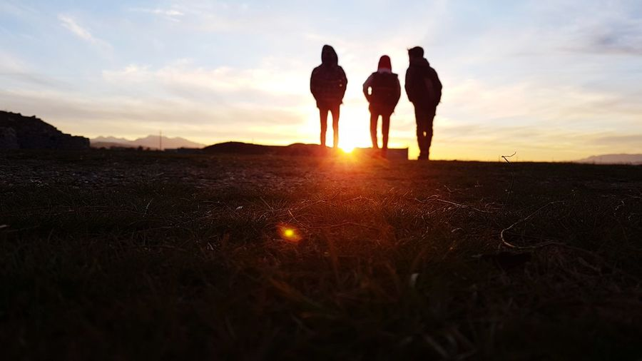 Silhouette family standing on land against sky during sunset