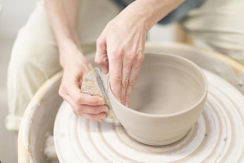 Midsection Of Craftsperson Molding Pot At Workshop