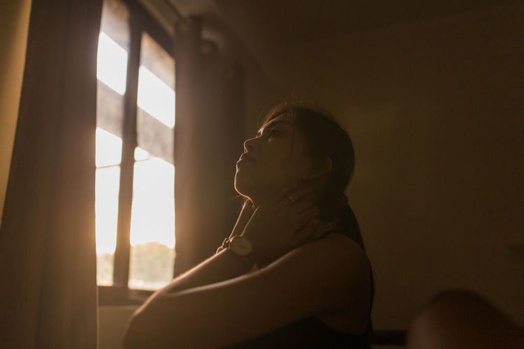 Young woman looking away by window at home